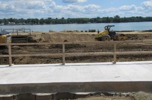 In the foreground is the first of the two steel sheet pile walls that make up the new dam in this area; the second is below the temporary railing for the concrete pad that sits on top of the concrete that fills the area between the two steel sheet pile walls. In the center, a dozer is spreading and compacting earth to build the jetty that will protect the channel. It will be covered with rip rap limestone. The earthen causeway beyond the dozer, which allowed vehicles to travel up and down the dam, will be removed once a prefabricated bridge is installed across the completed new channel. Below right, the trash cage is now in place. The hinged top, which allow debris to be removed, is still open. Below left, technicians check the compaction of the earthen base for the jetty that will protect the new channel from wave action.