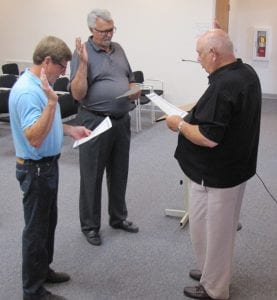 Hebron Mayor Mike McFarland, right, administers the oath of office to returning council members Tom Marietta, left, and Jim Layton, center. Beacon photo by Charles Prince.